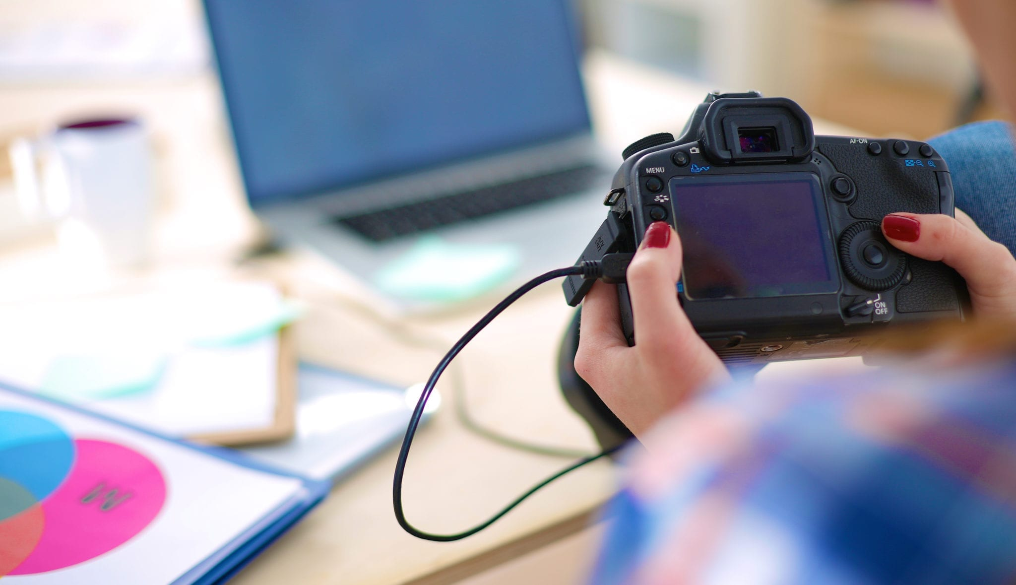 Photo of a camera being held over a desk with a laptop on it